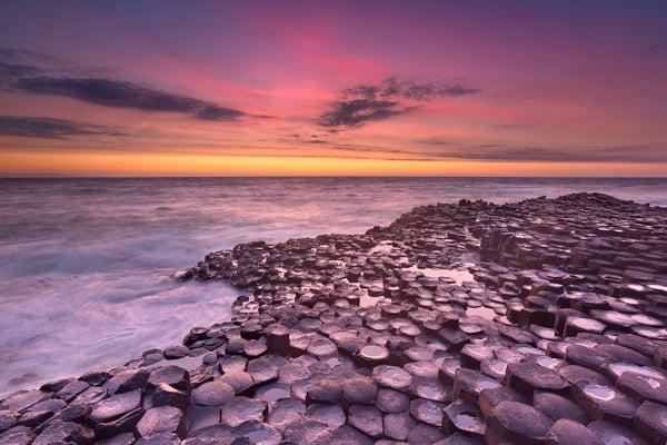 A sunset over a flat rocked beachside in Ireland.