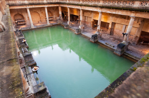A beautiful full view of the roman baths, filled with water that's reflecting the sky.