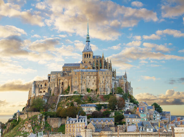 Mont St. Michel, a castle-like grey building with blue roofs, overlooking the small town weaving down the hill on a cloudy day.