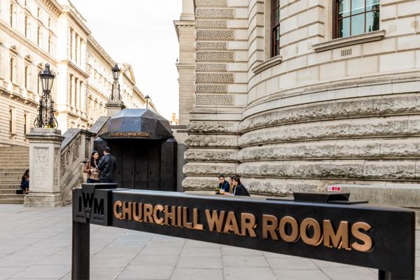A few people standing by the sign and building for the Churchill War Rooms.
