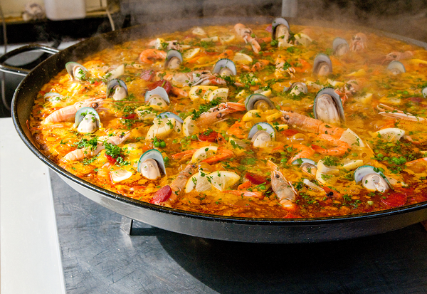 A wide dish with a yellowy-red sauce, shrimp, and oysters called Paella.