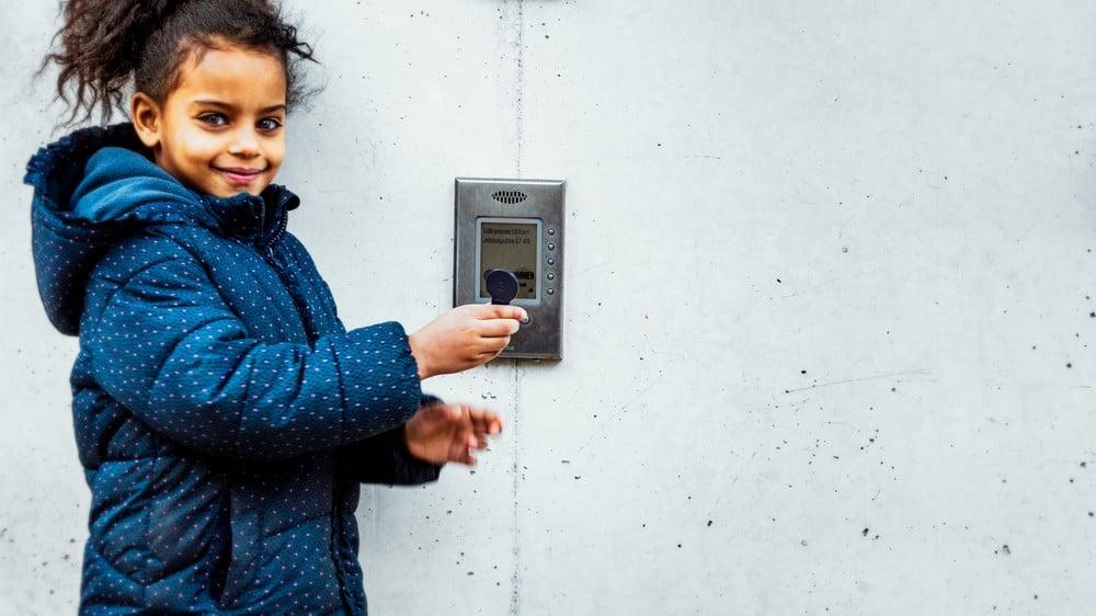 Jente betjener porttelefon fra Aptus med nøkkelbrikke ved inngang til borettslag sameie.