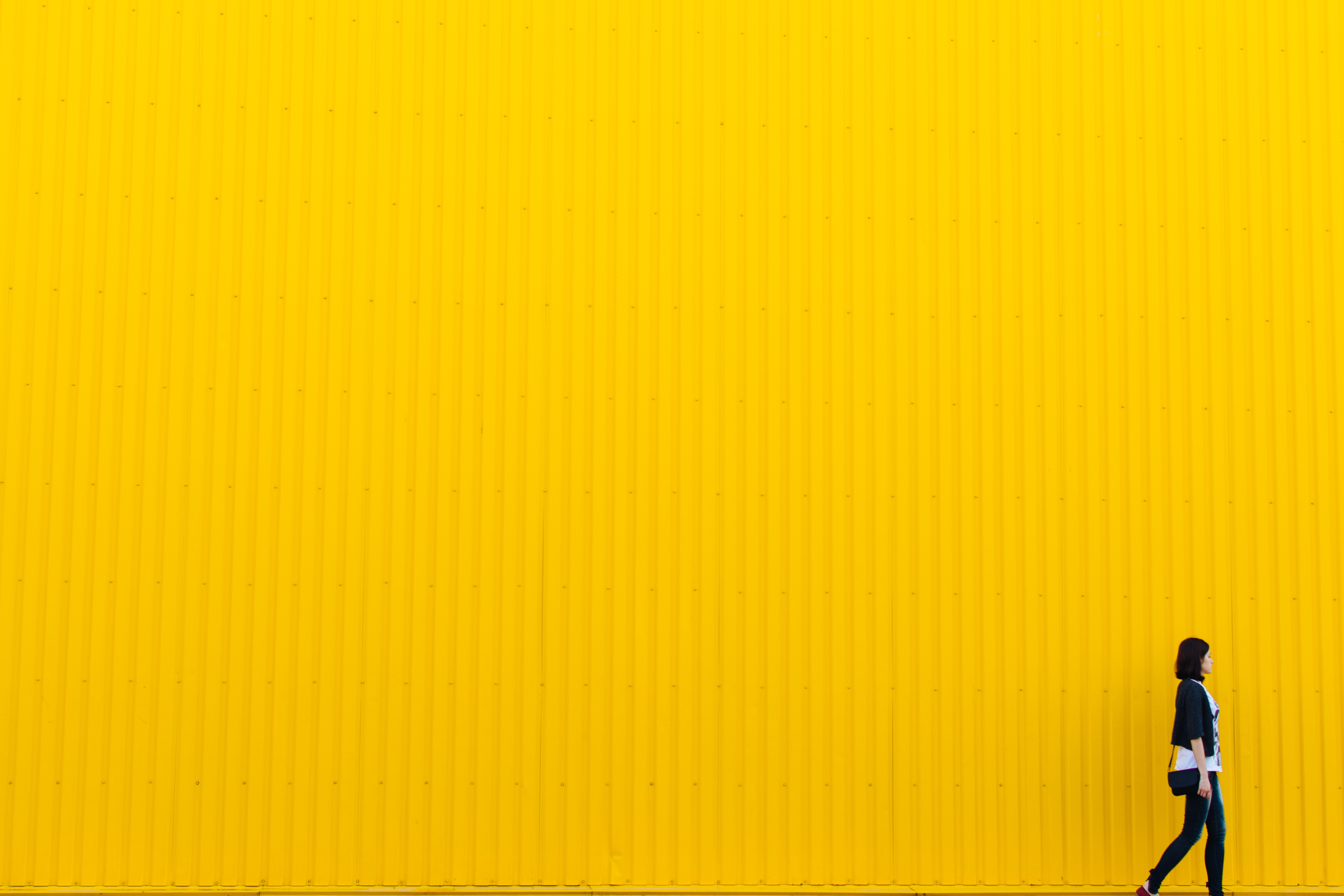 Woman standing next to yellow wall