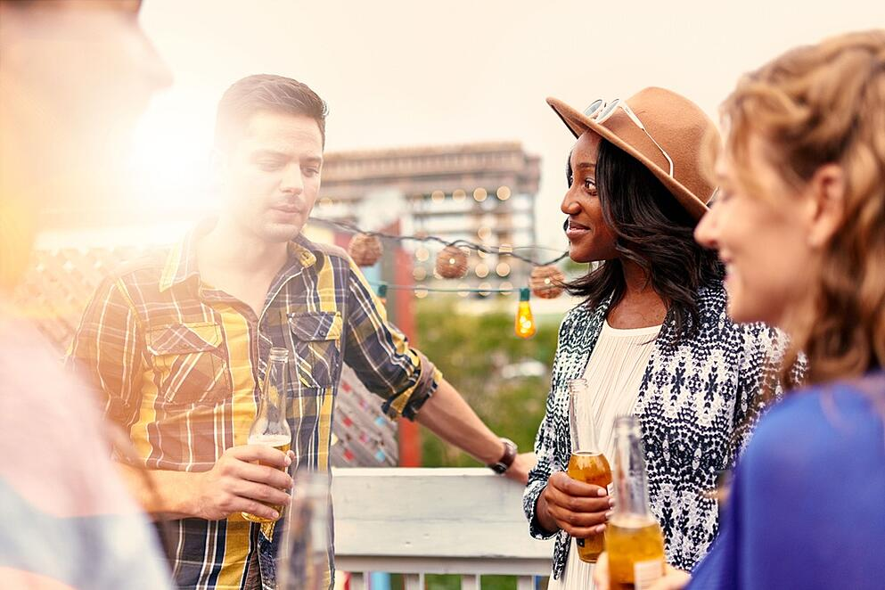 Multi-ethnic millenial group of friends partying and enjoying a beer on rooftop terrasse at sunset.jpeg