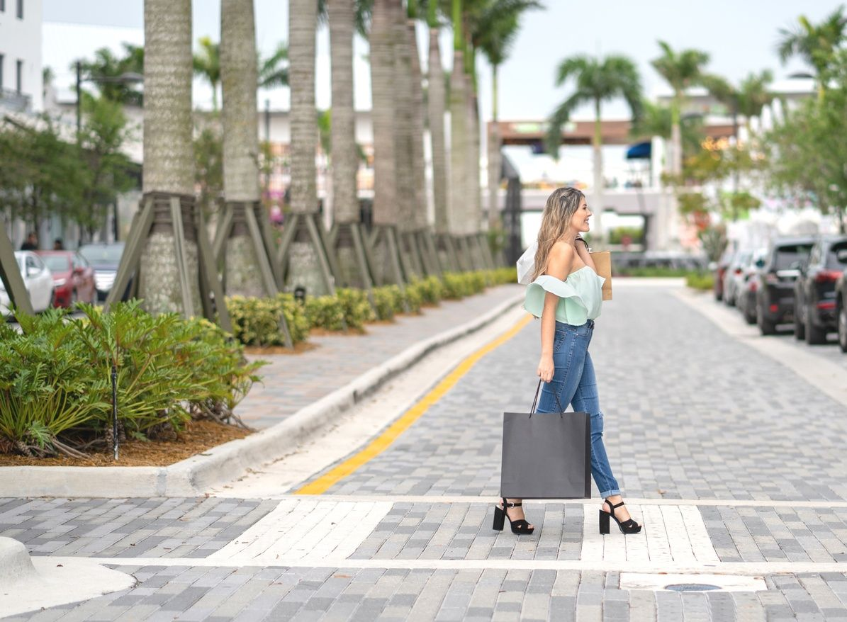 woman holding a shopping bag and crossing the street in Coral Gables