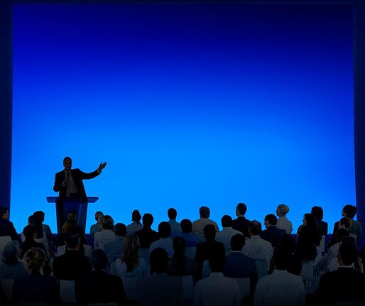 Speaker Standing at a Podium and Speaking to an Audience at a Conference