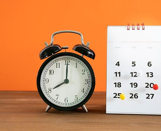 retro-alarm-clock-and-calendar-on-wooden-table-with-orange-background-picture-id1153209621-1
