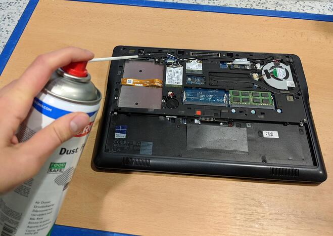 Cleaning the inside of a laptop using compressed air.
