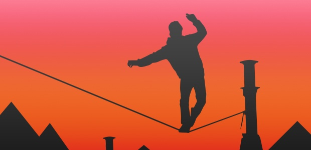 Silhouette of a man balancing on a tightrope against an orange sky.