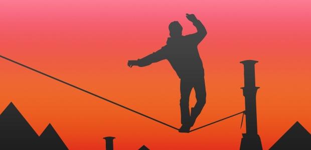 Silhouette eines Mannes, der vor einem orangefarbenen Himmel auf einem Drahtseil balanciert.