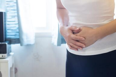 A Woman in the bathroom with stomach pain