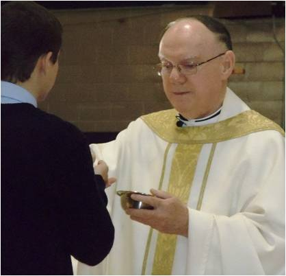 student-receives-communion-from-Bishop-Coleman