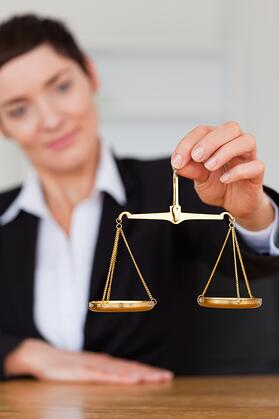 Serious woman holding the justice scale in her office
