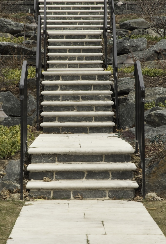 Stone and concrete stairway with black iron railings up rocky hillside