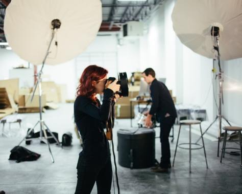 Videomaker che filma con una telecamera un contenuto video localizzato