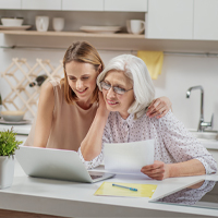 Adult daughter helping senior mother choose the right senior living community by looking at the Kendal at Granville website.