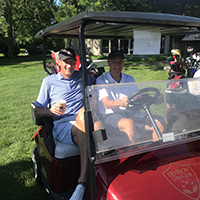 Two men sitting in a golfcart waiting to play golf