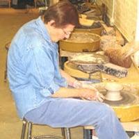 Adult woman spinning on ceramics wheel