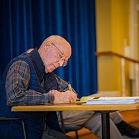 Older man taking notes during a resident driven committee meeting