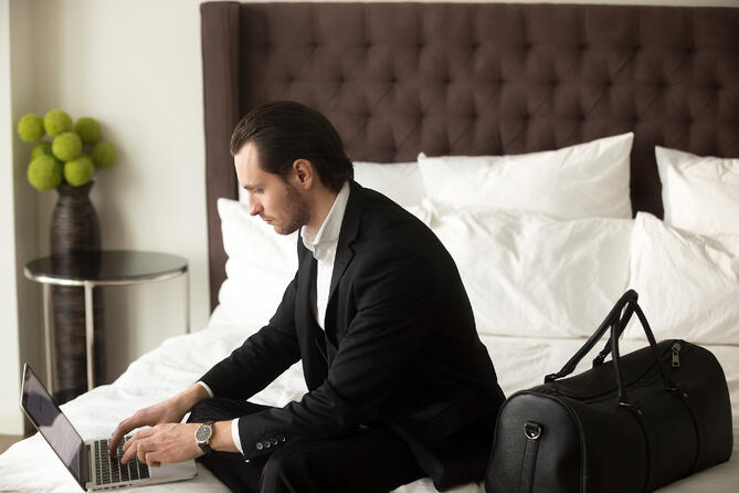 bigstock--188457985--business-man-working-from-hotel-while-travelling