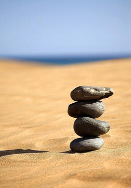 balancing stones on a sunny day at the beach
