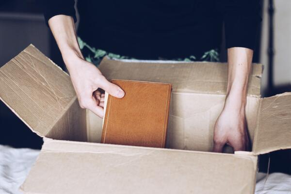 woman packing a book into a moving box