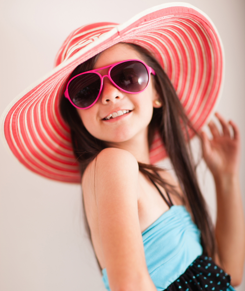 Fashion summer girl wearing a hat and posing for the camera