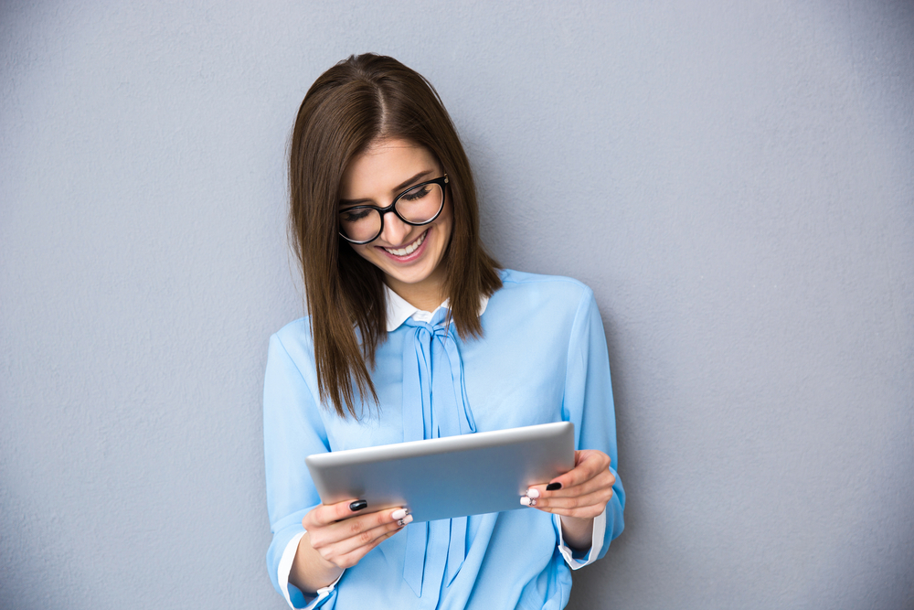 Happy businesswoman standing with table computer over gray background. Wearing in blue shirt and glasses.