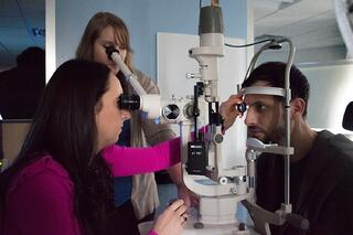 Regional Sales Representative, Lena Zhuk, receives assistance from Dr. Stephanie Leburg adjusts her slit lamp to get a perfect retinal view on PCO student Kyle Keyser .