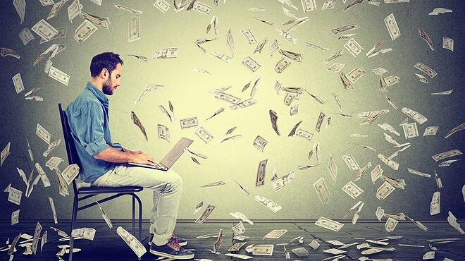 Young man using a laptop building online business making dollar bills cash falling down. Beginner IT entrepreneur under money rain. Success economy concept .jpeg