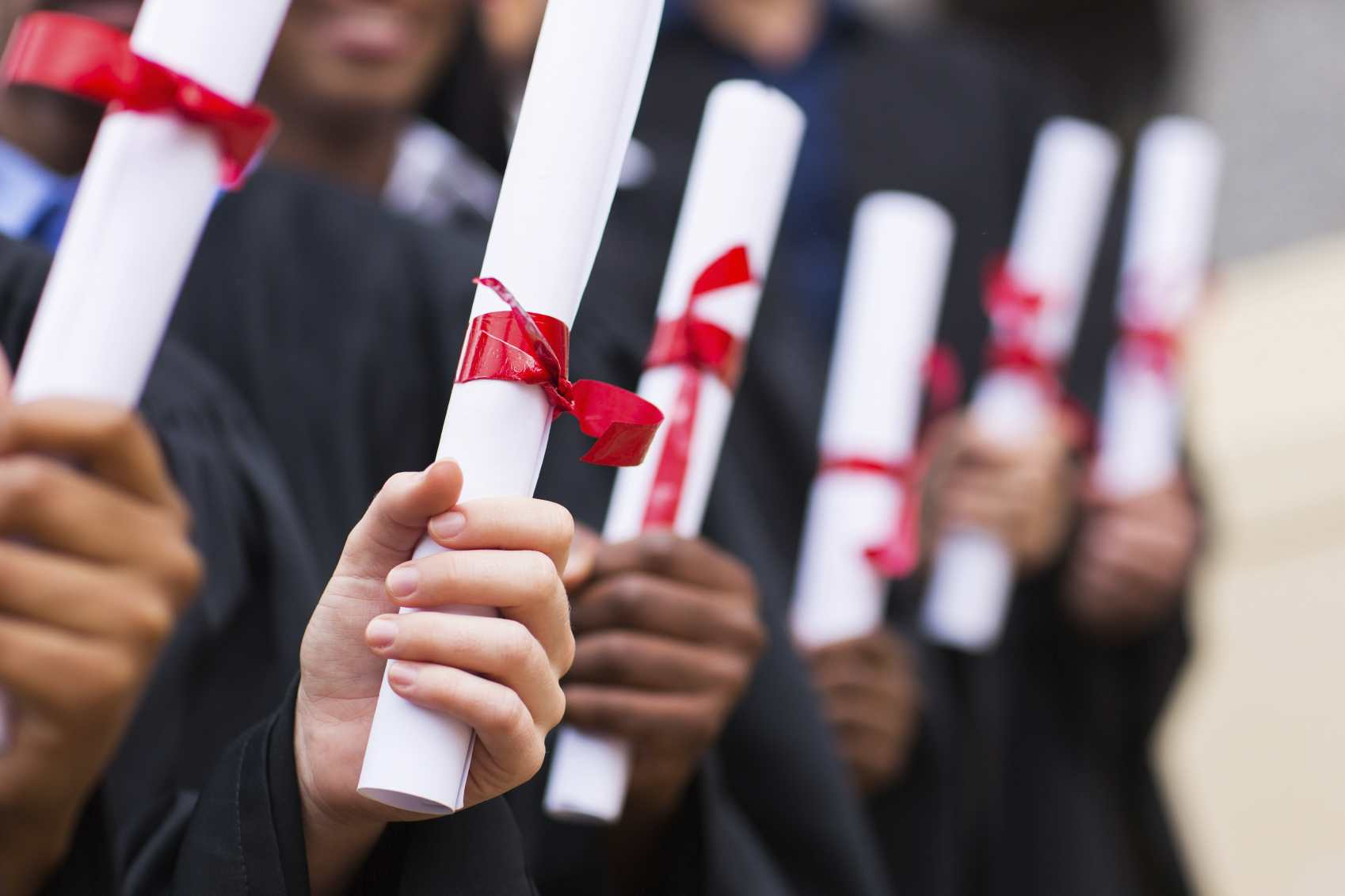 row of college graduates holding diplomas