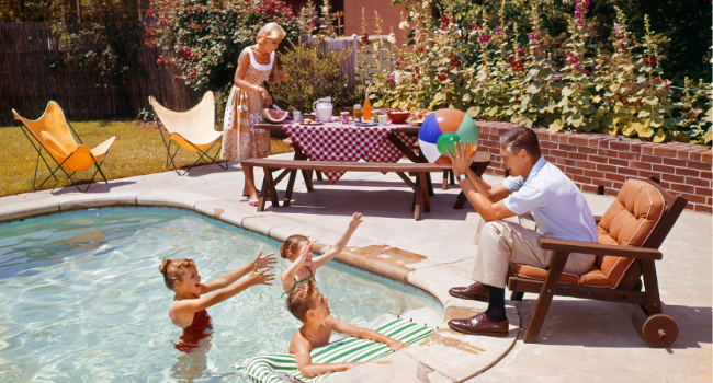 Vintage image of a family playing in a pool with a picnic setup on a picnic table.