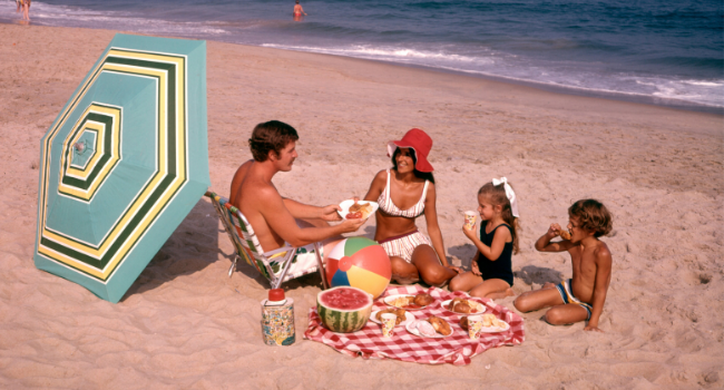 Vintage image of family on a beach enjoying a picnic.