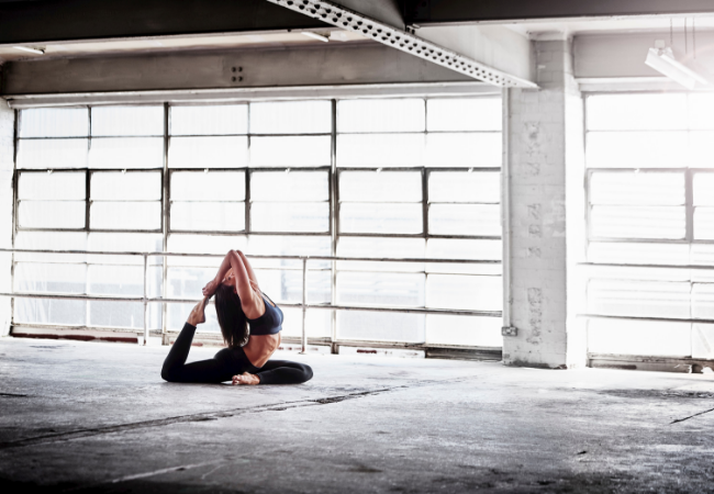 Woman practicing yoga pose in front of warehouse window