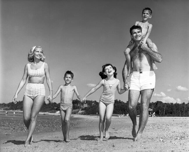 Family with three kids walking on beach