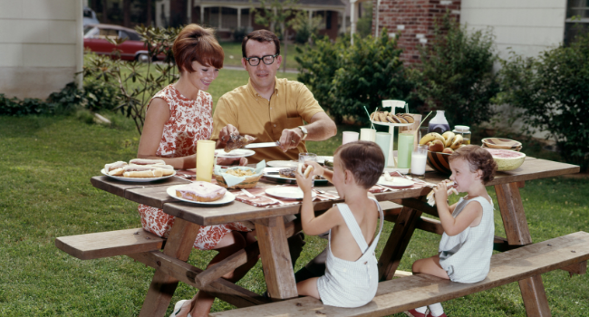 Stock image of a family sitting at a picnic table.