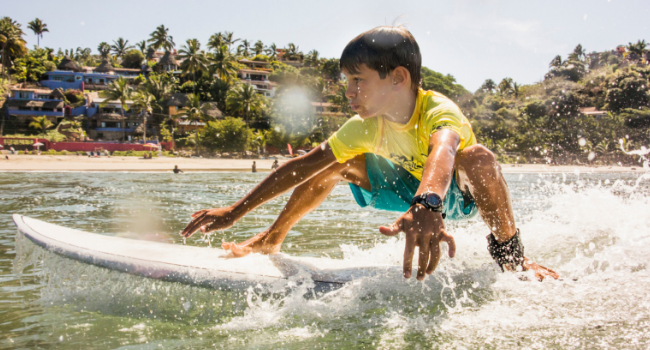 Young boy surfing in ocean