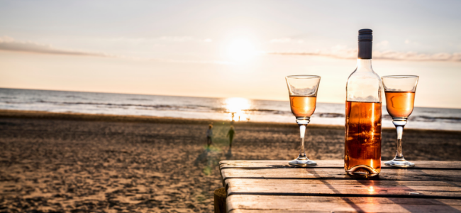 a bottle of rose' and two glasses on beach with sunset