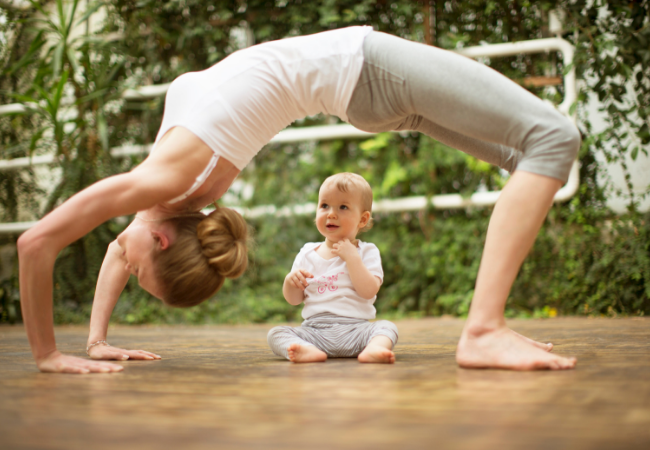 Woman doing yoga exercise while baby watching her