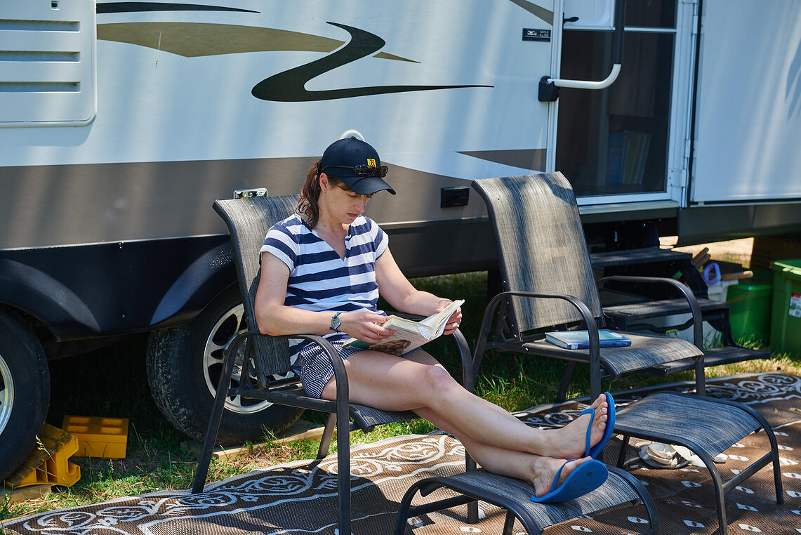 Woman reading book outside an RV