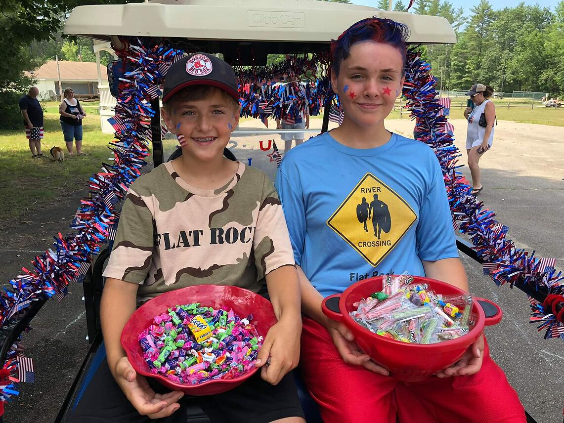 Two boys on golf cart with Fourth of July decorations