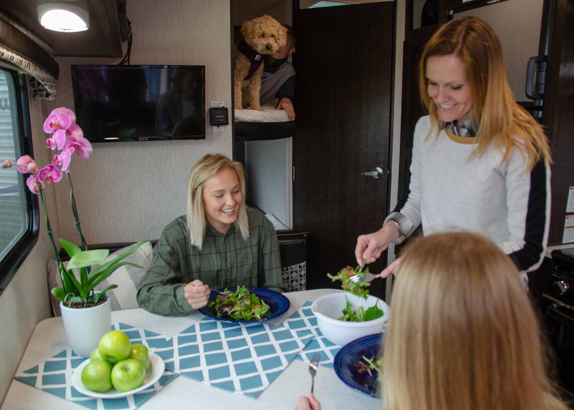 Mother serving daughters salad in RV