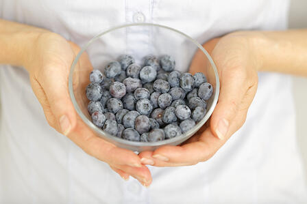 Close up of woman hands holding a glass bowl of fresh Blueberries