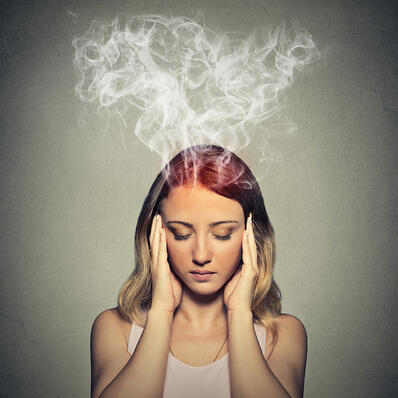 Portrait young stressed woman thinking too hard steam coming out up of head isolated on grey wall background. Face expression emotion perception