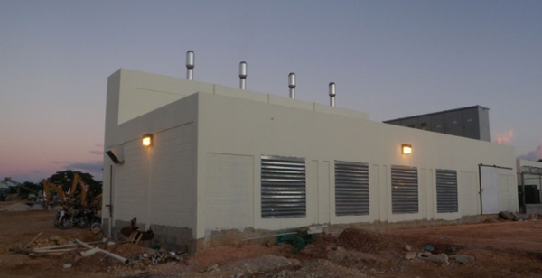 Exterior shot of a noisy generator room in need of noise abatement. Noisy generator facility incorporating louvered Acoustiblok All Weather Sound Panels® to reduce external noise.