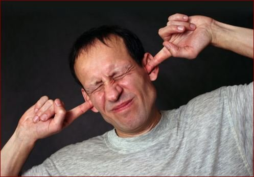 man plugging ears from noise
