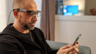 A man in the CTI UX lab, wearing eye tracking glasses and holding a mobile phone