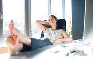 businesswoman-in-her-office-sitting-with-legs-on-PV6KJ3D