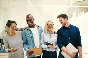 laughing-group-of-diverse-businesspeople-standing-UK96MFS