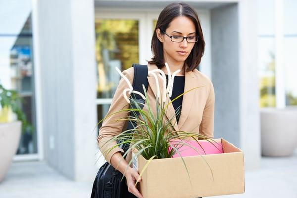 redundant-businesswoman-leaving-office-with-box-PQ7RQ7W